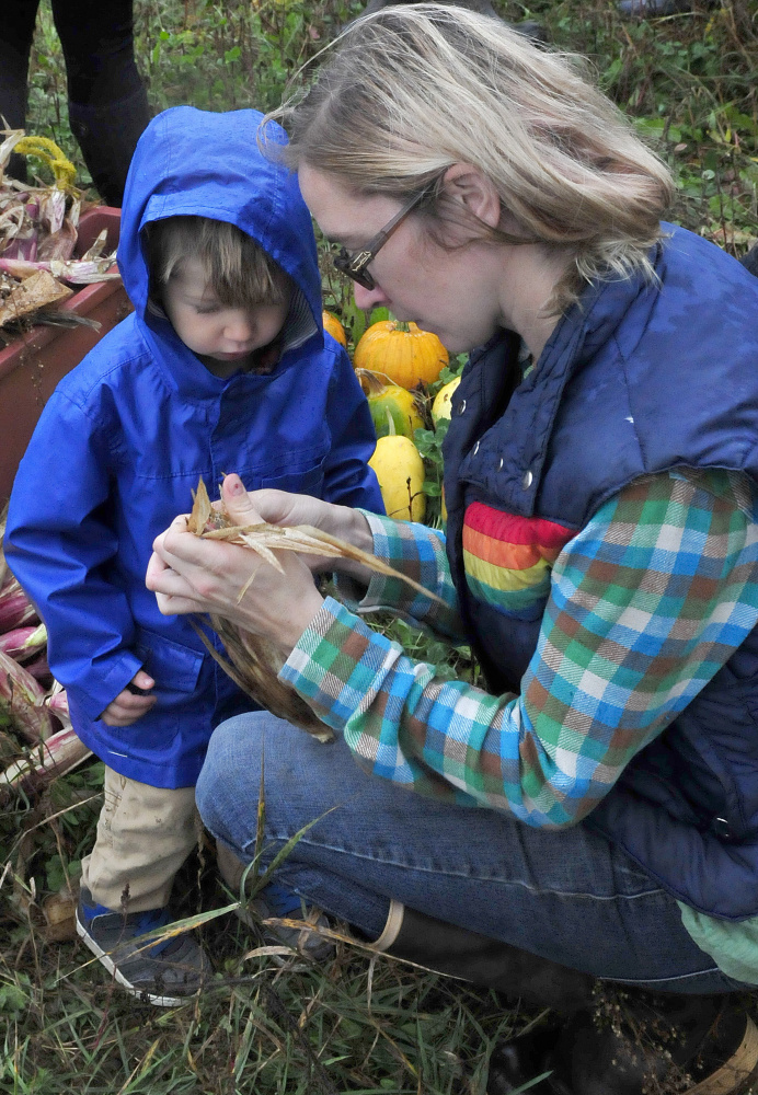 Cate Jacques shows her son Theodore corn grown using the Three Sisters technique of planting corn, squash and beans in a single mound, during an Indigenous Peoples Day celebration at the Sweet Land Farm in Starks on Monday.