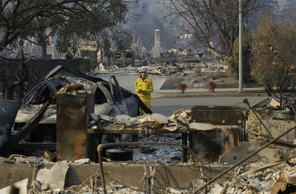Cal Fire forester Kim Sone inspects damage at homes destroyed by fires in Santa Rosa, Calif., on Thursday. Gusting winds and dry air forecast for Thursday could drive the next wave of devastating wildfires that are already well on their way to becoming the deadliest and most destructive in California history.
