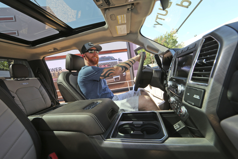 A man checks out a fully-loaded F-450 Super Duty Limited, the biggest version of the Ford F-Series, on display at the State Fair of Texas in Dallas. Buyers are increasingly looking for pickups with all the comforts of luxury cars, from backup cameras to panoramic glass roofs.