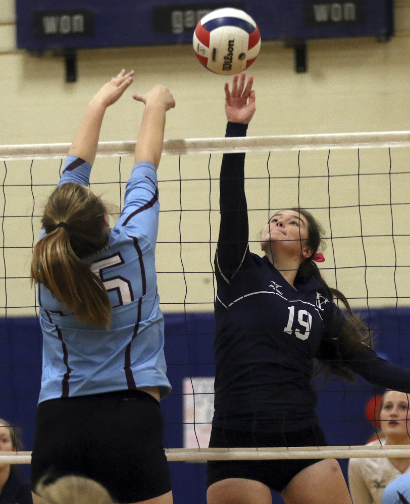 Ceanne Lyon, right, of Yarmouth tips the ball over the net as Windham's Meghan Harmon defends during a volleyball match Thursday in Yarmouth. Yarmouth, ranked No. 2 in Class B, defeated the Class A Eagles in three sets to improve to 12-1.