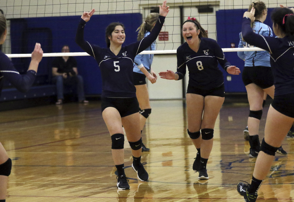 Yarmouth's Morgan Cooper, left, and Nora Laprise celebrate after the Clippers won a point on their way to a 25-19, 26-24, 25-16 victory.