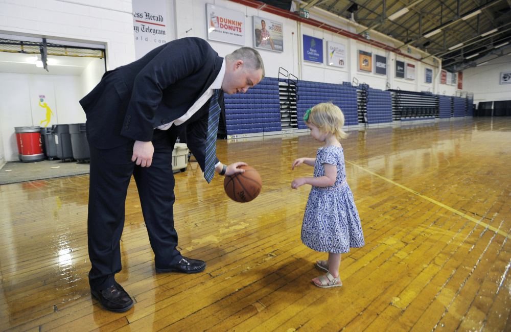 Brandon Bailey plays with his daughter Kary, 3, at the Portland Expo on Thursday prior to a news conference where Bailey was announced as the Red Claws' new head coach. Staff photo by Shawn Patrick Ouellette