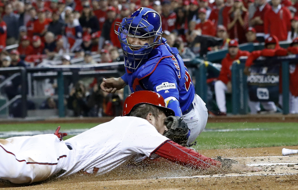 Chicago catcher Willson Contreras tags out Washington's Trea Turner at home on a infield grounder by Bryce Harper in the first inning.