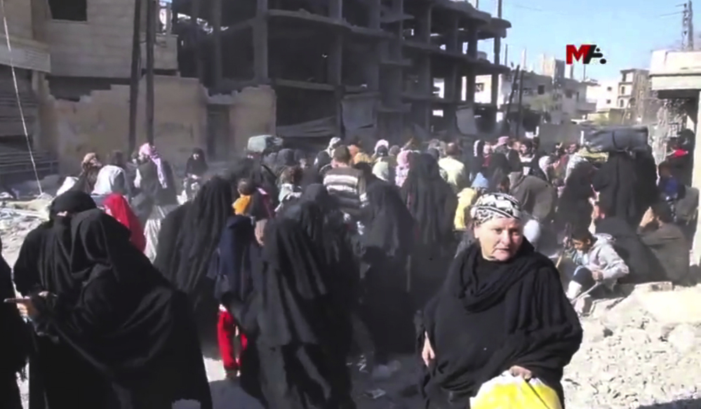 This frame grab from a video provided Friday by Turkey-based Kurdish Mezopotamya agency media outlet shows Syrian civilians who fled from the areas that are still controlled by the Islamic State militants in Raqqa, Syria.