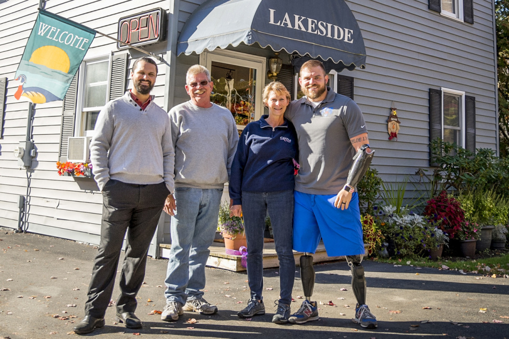Zach Stewart, far left, and Army veteran Travis Mills, who lost his arms and legs in an explosion, are the new owners of Lakeside Motel & Cabins. They are joined by Mills' parents, Dennis and Cheri Mills, who will help maintain the motel and cabins in East Winthrop.