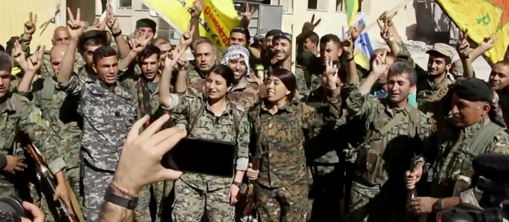 Kurdish fighters celebrate in Raqqa, Syria, once the heart of the Islamic State's caliphate.