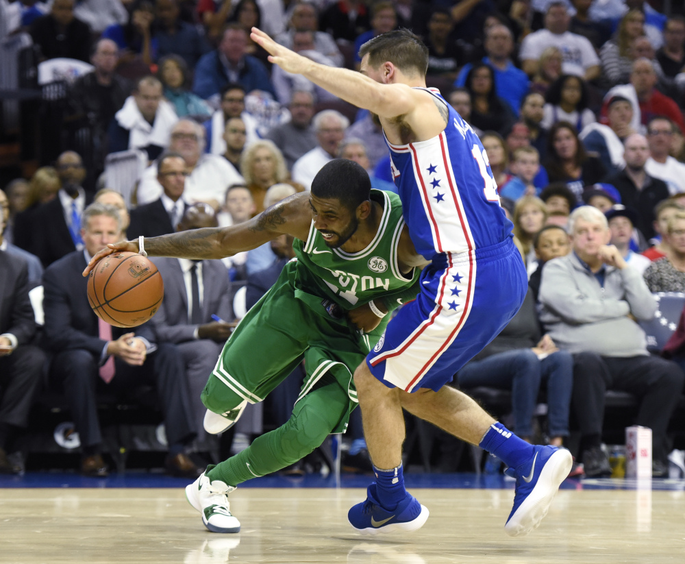Boston's Kyrie Irving, left, drives to the basket past Philadelphia's T.J. McConnell in the first half Friday night in Philadelphia.