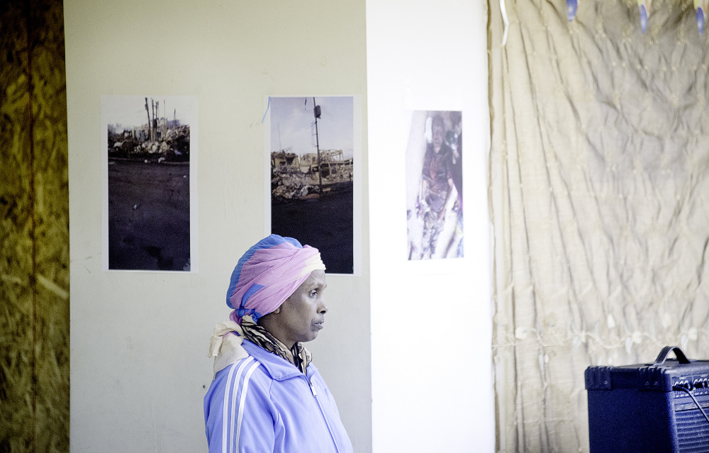 Maryam Mohamed stands Friday night in front of pictures of the destruction caused by terrorist bombings in Mogadishu, Somalia, on Oct. 14.