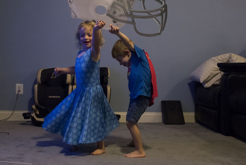 Alyssa Schlomer, 3, dances with her twin brother, Logan, at the Schlomer family's home in Lexington Park, Md.