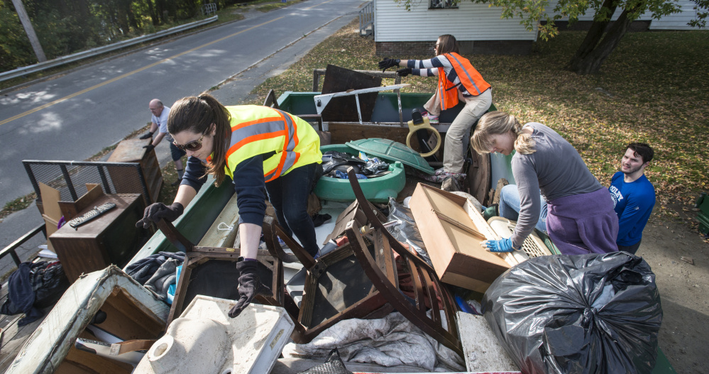 Colby College staff members Laura Jones-Pettit, left, and Katie Sawyer, and Megan Marsh, back, organize a large metal bin of old household and yard goods collected Saturday for a cleanup designed to help students and faculty engage with the city of Waterville.
