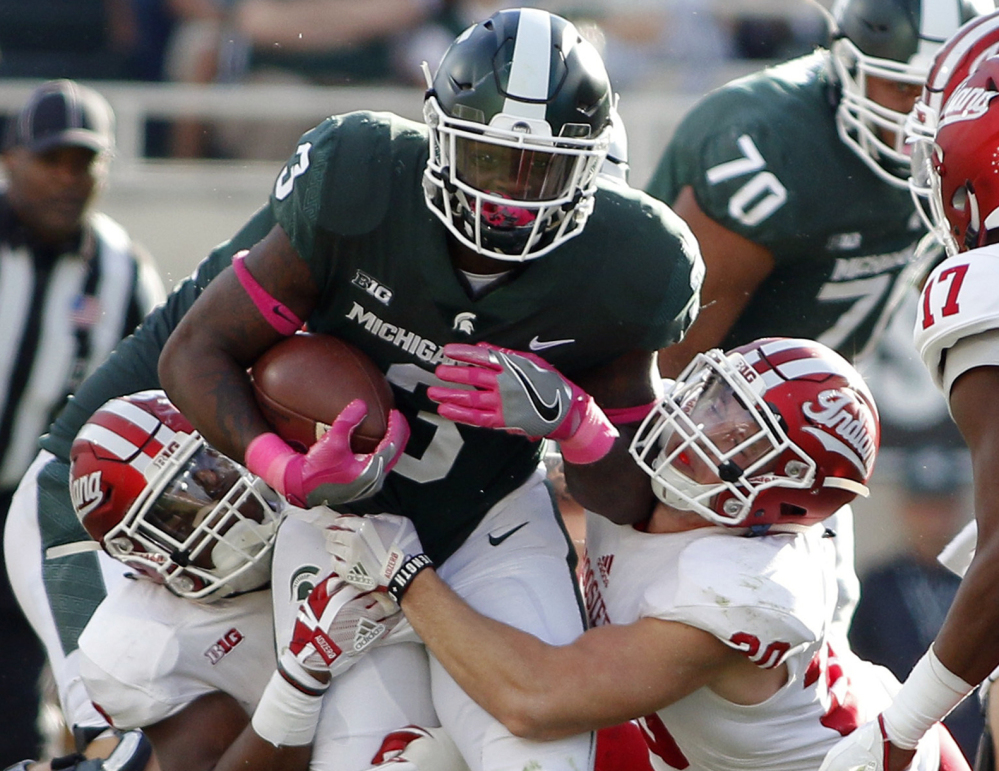 L.J. Scott of Michigan State is stopped by Nathanael Snyder, left, and Chase Dutra of Indiana during the second quarter of 18th-ranked Michigan State's 17-9 victory in a Big Ten game Saturday.