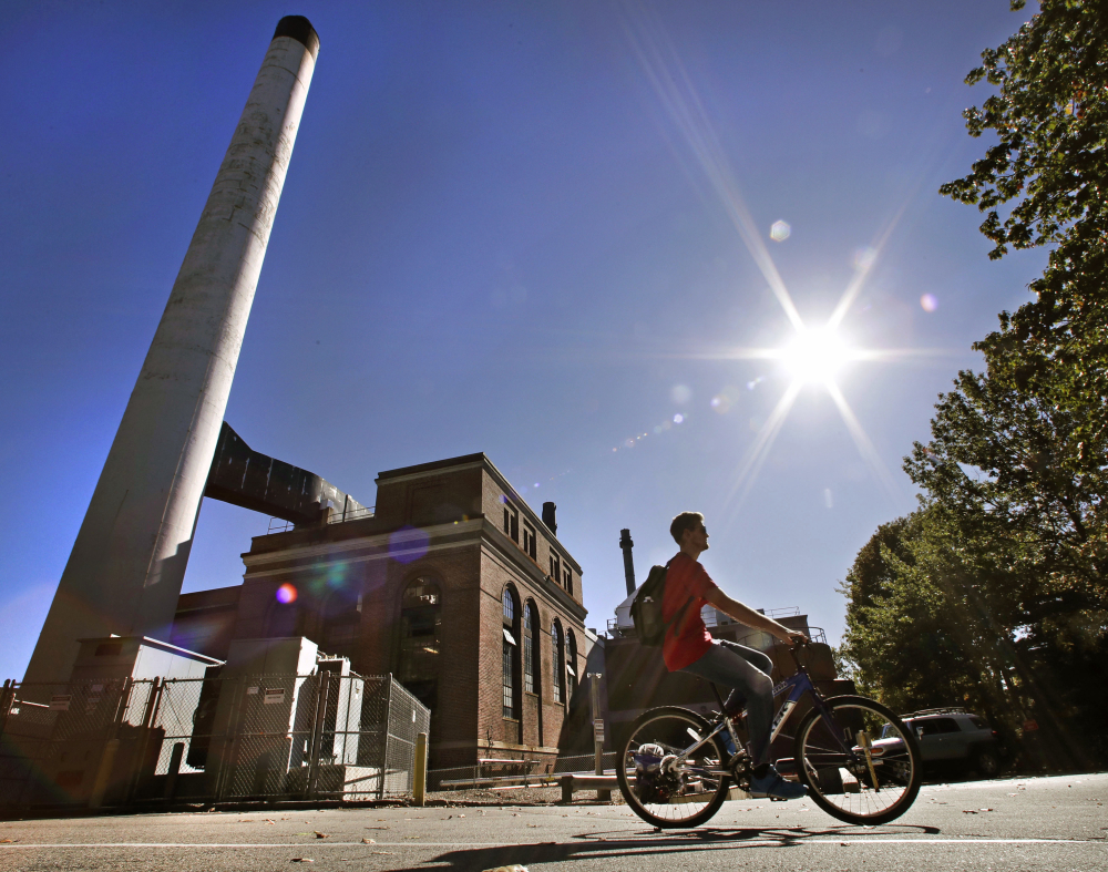 A student cycles past the UNH Cogeneration Facility last week at the University of New Hampshire in Durham. The school won prestigious recognition for having a campus powered entirely by renewables and recycling up to 25,000 pounds of food each month.