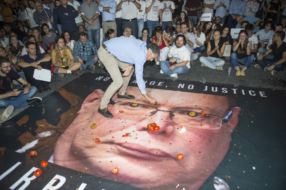 A banner with a photo of Malta Police Commissioner Lawrence Cutajar is on the floor outside the Malta Police Headquarters as people throw coins, tomatoes and cheesecakes at it and at the facade during a rally to honor anti-corruption reporter Daphne Caruana Galizia, killed by a car bomb on Oct. 16, in Valletta, the capital city of Malta, on Sunday.