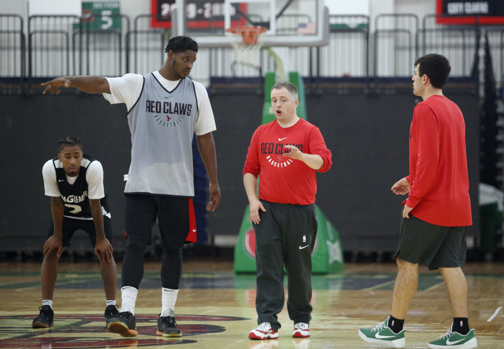 In his first practice as a basketball head coach, Brandon Bailey, center, talks with Devin Williams, one of the 15 players who attended the opening day of training camp Monday for the Maine Red Claws at the Portland Expo.