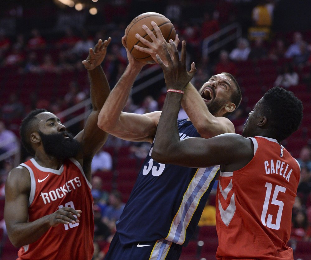 Marc Gasol of the Memphis Grizzlies looks for room Monday night while being guarded by James Harden, left, and Clint Capela of the Houston Rockets during the first half of Memphis' 98-90 victory on the road.