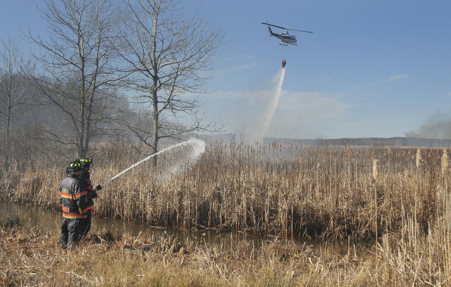 Firefighters battle a brush fire in Old Orchard Beach on April 15, 2016, that was fanned by strong wind. Ricky Plummer, who was the town's fire chief at the time, pleaded guilty Wednesday to setting the fire.