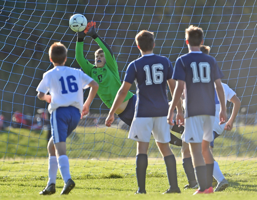 Mt. Blue goalie Tucker Carleton makes a save against Messalonskee High School in Oakland earlier this season as Dom Giampietro (16) and Alden Thompson Vought (10) look on.