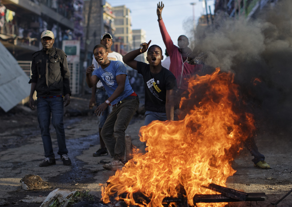 Opposition protesters taunt riot police to come and get them, as they stand behind a burning barricade during clashes in the Mathare slum of Nairobi, Kenya, on Thursday.