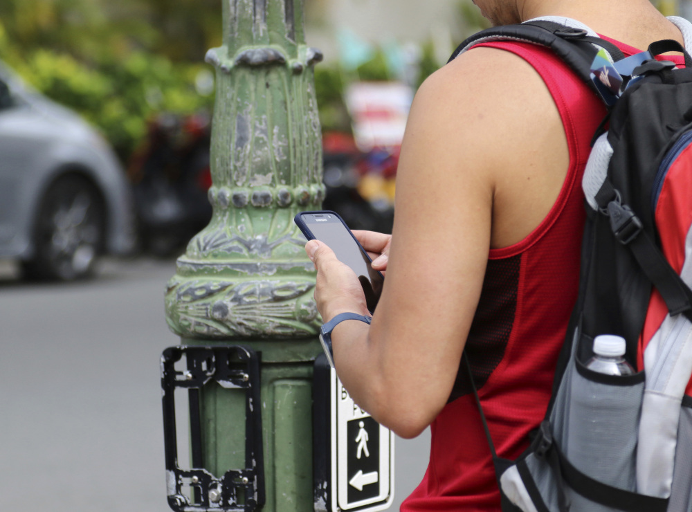 A man uses his cellphone before crossing a street in Honolulu on Wednesday. A new ordinance allows police to issue tickets to pedestrians caught looking at a cellphone or electronic device while crossing a city street. Associated Press/Caleb Jones