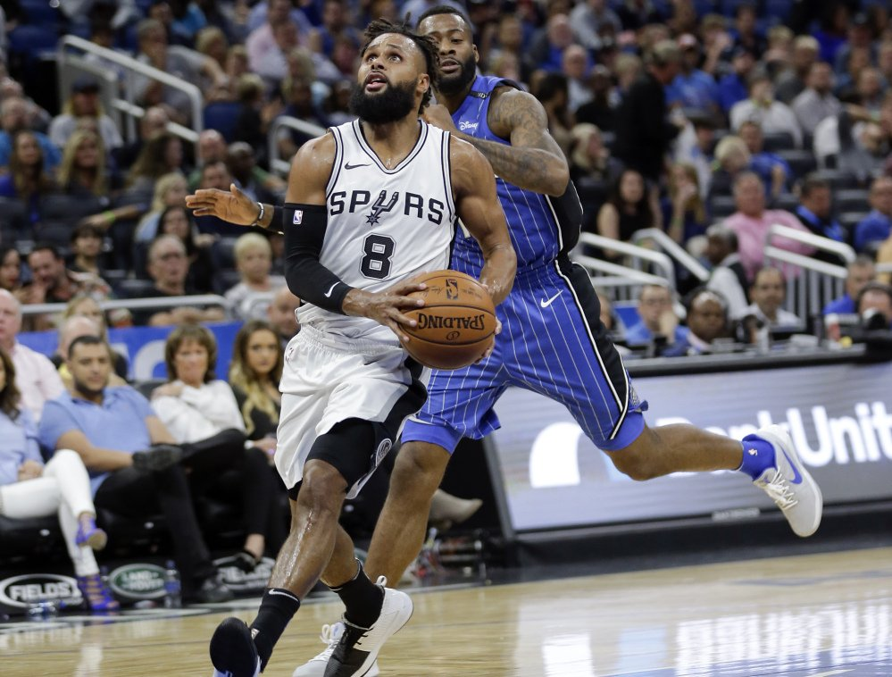 San Antonio's Patty Mills runs past Orlando's Jonathon Simmons during the second half of the Magic's 114-87 win Friday in Orlando, Florida.