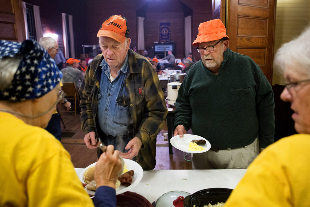 Wayne Weeks, left, and Steve McDuffie fill up their plates Saturday during the hunter's breakfast in St. Albans.