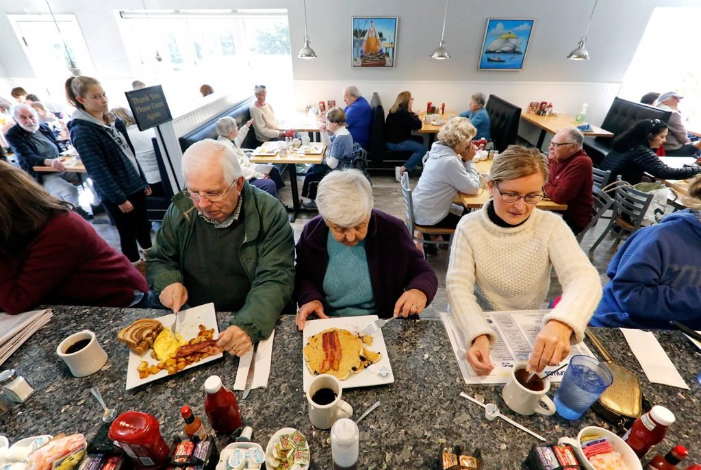 Nelson and Dottie Megna, left, of Portland's Deering neighborhood share a counter at Bernie's Foreside with Diane Thornton-Chandler of Cumberland. All three were without power Tuesday morning. The restaurant has had higher-than-normal volume since the power outages began early Monday morning.