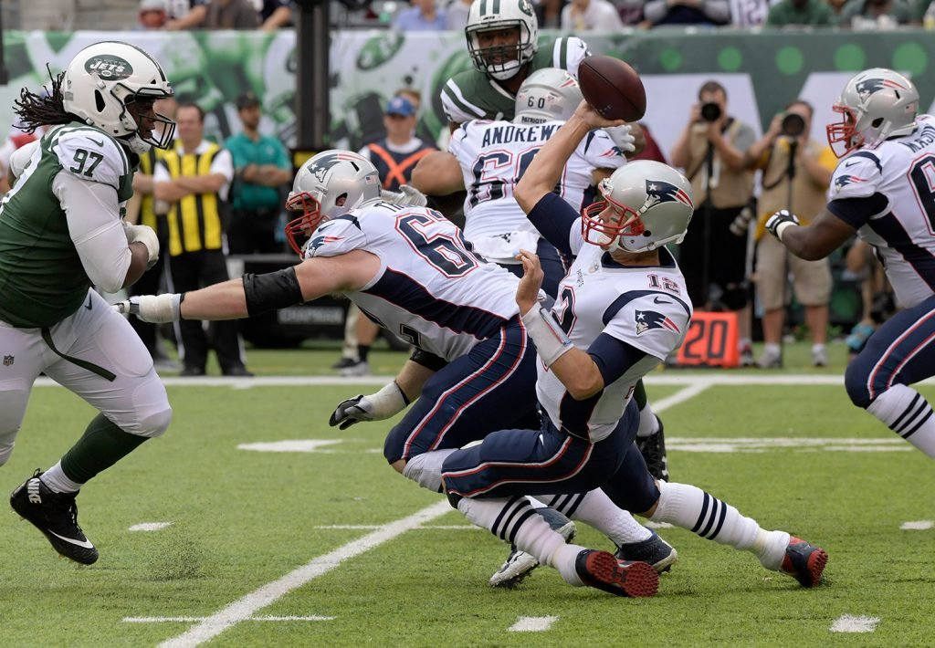 Tom Brady throws a pass while falling to the turf as Jets defensive end Ed Stinson closes in during Sunday's game. The Patriots got out with a win, but they're far from the team that some predicted would go undefeated this year.