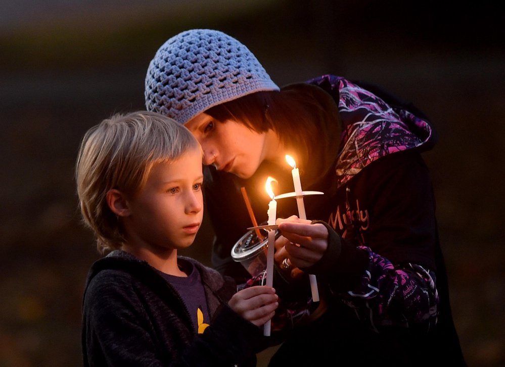 Jessica Hainer, who described herself as a victim of domestic violence, helps to light the candle of her daughter, Shayla, 8, during a domestic violence awareness candlelight vigil Thursday at the gazebo at Coburn Park on Water Street in Skowhegan.