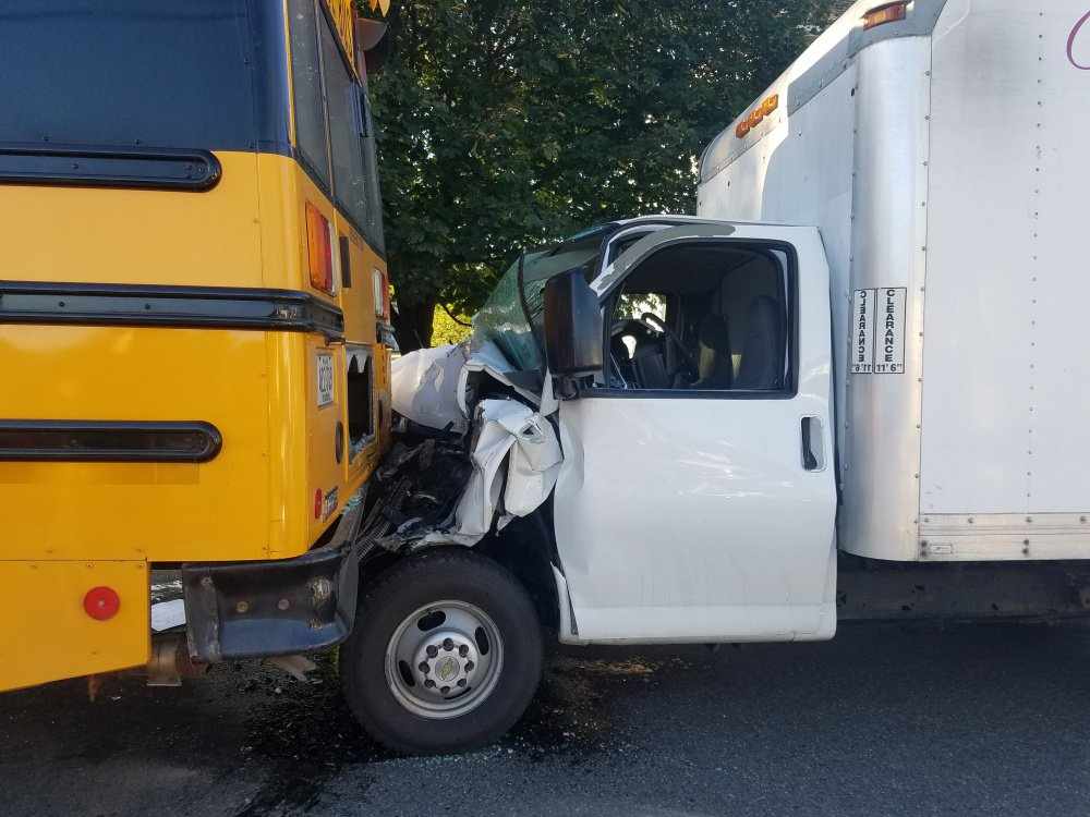 Sun glare blinded the driver of a box truck that crashed into the rear of a school bus Tuesday in Waterville with 13 children on board the bus.