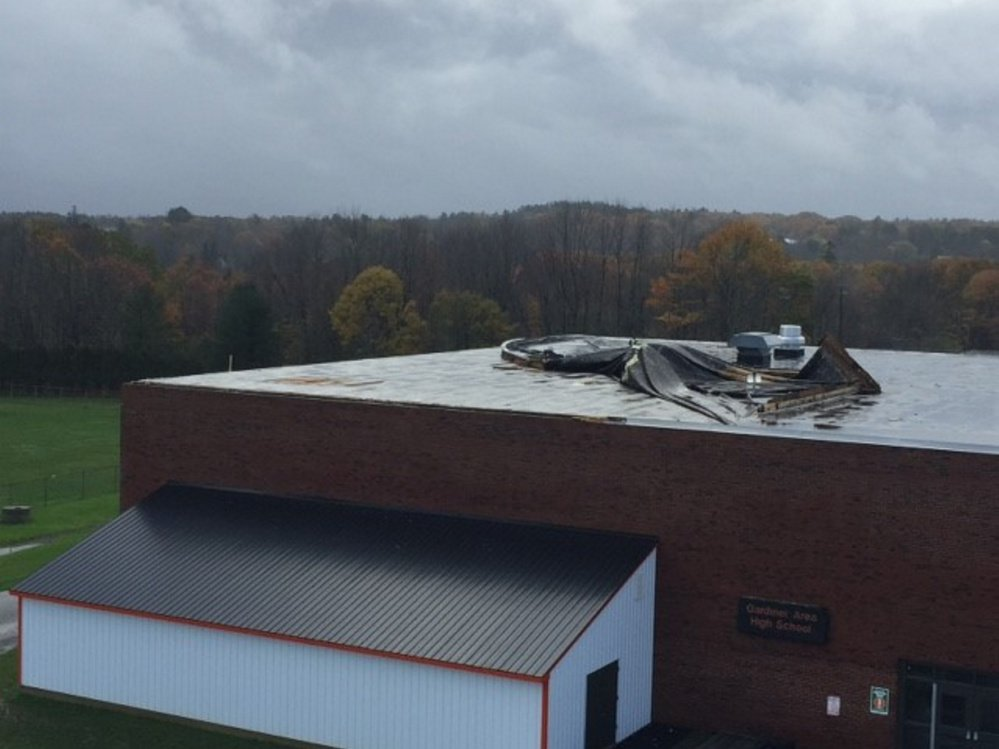 Damage can be seen atop the Gardiner Area High School roof on Monday following a destructive storm that swept through the region.