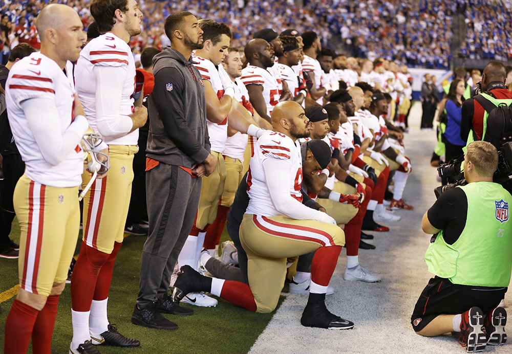 About a dozen members of the San Francisco 49ers take a knee during the playing of the national anthem before an NFL football game against the Indianapolis Colts on Sunday in Indianapolis.
