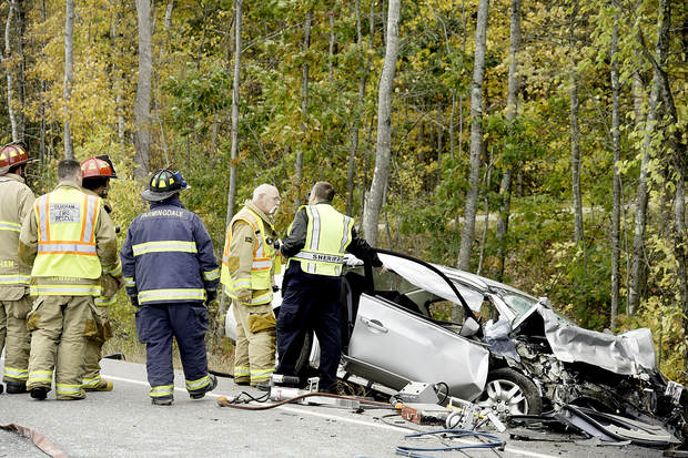 Rescue personnel respond to the fatal crash on Route 136 in Durham on Monday.