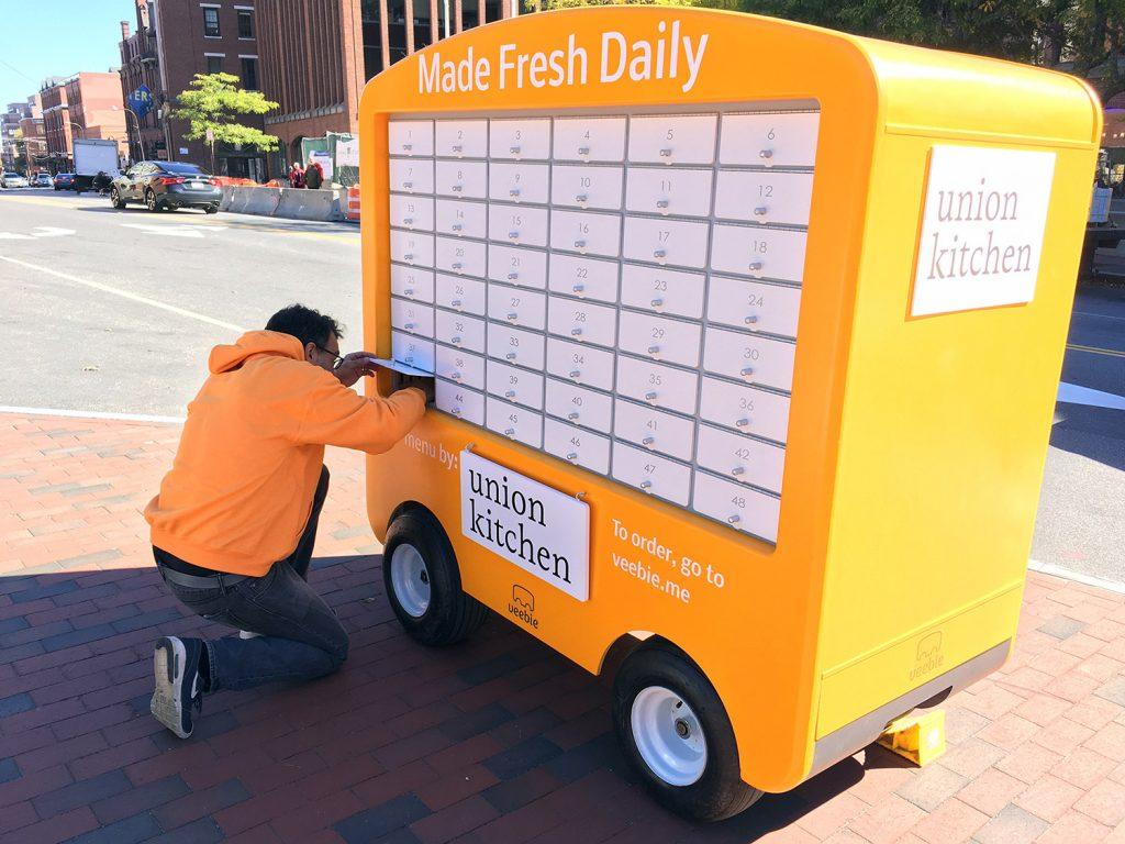 Yona Belfort, vice president of engineering at Veebie, Inc., stocks his company's food cart with a prepared lunch from Union Kitchen.