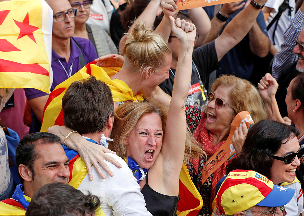 People in Barcelona celebrate as they watch giant screens televising the Catalan regional parliament voting to declare independence from Spain.