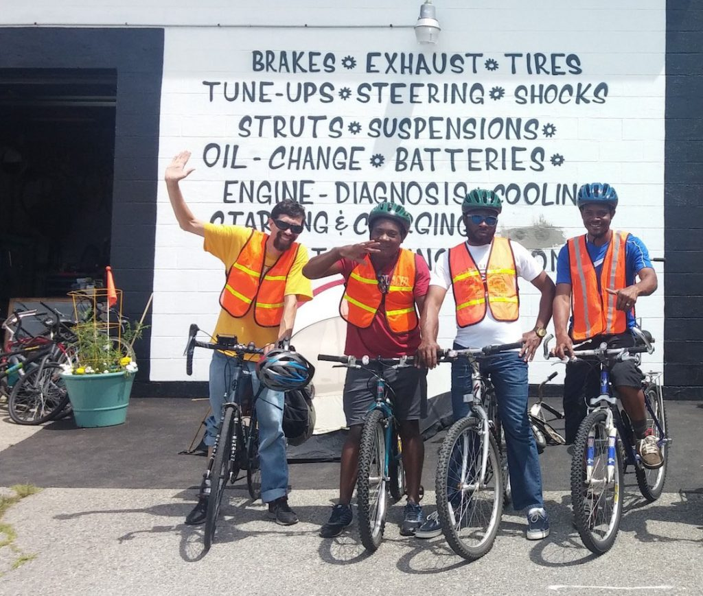 Bikes For All Mainers participants celebrate graduation in July, outside Portland Gear Hub on Washington Ave. From left are instructor John Brooking of the Bicycle Coalition of Maine; Claude Shambare, JOB Mbemba, and Paulo Celestino.