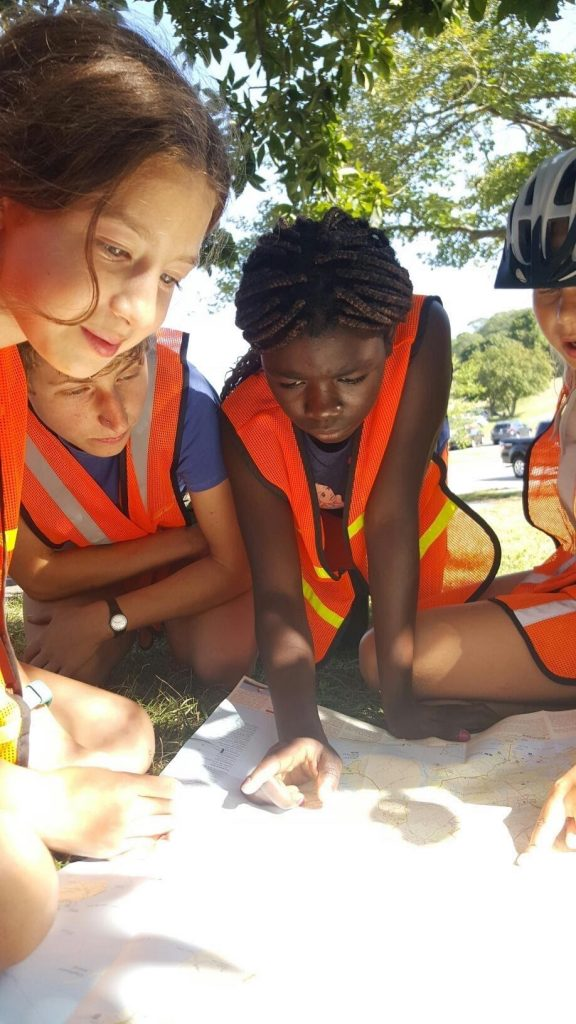 Ainsley Judge, second left, looks on as Calia Brown, Orlane Zouri and Cora Johnson map out a bicycle route at Girls Mountain Bike Camp, a Bike School program, over the summer.