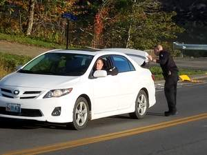 A police officer searches a car in Thomaston on Wednesday morning.  Stephen Betts/Village Soup