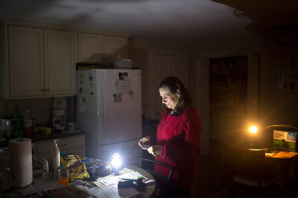 Brenda Sherwin stands in her kitchen in Cumberland at dusk Thursday, illuminated by battery-powered lanterns. She and her husband haven't had power since early Monday morning. Four days isn't the longest they have been out of power. The couple had no power for 10 days after the ice storm in 1998. Sherwin, who does day care in her home, said,