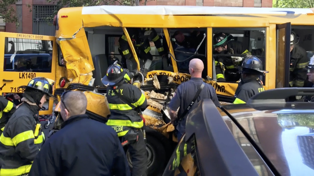 Emergency personnel work on a school bus after it was rammed by a driver in New York on Tuesday.