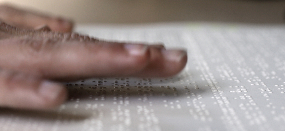 Proofreader Georgie Sydnor runs her fingers over Braille at the National Braille Press in Boston. The organization has been a leading force for Braille literacy in the U.S. since its founding as a weekly newspaper for the blind in 1927.
