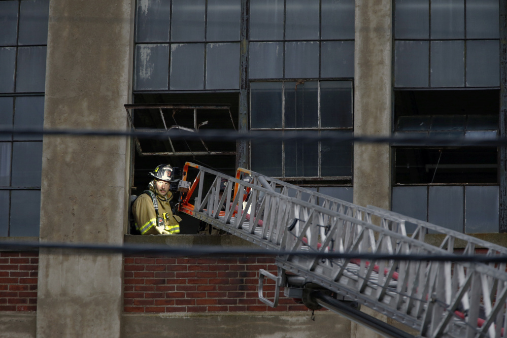 A Sanford firefighter is illuminated by a ladder truck while responding to a fire at the vacant Stenton Trust mill on Thursday. Fires have been a frequent occurrence recently in Sanford.