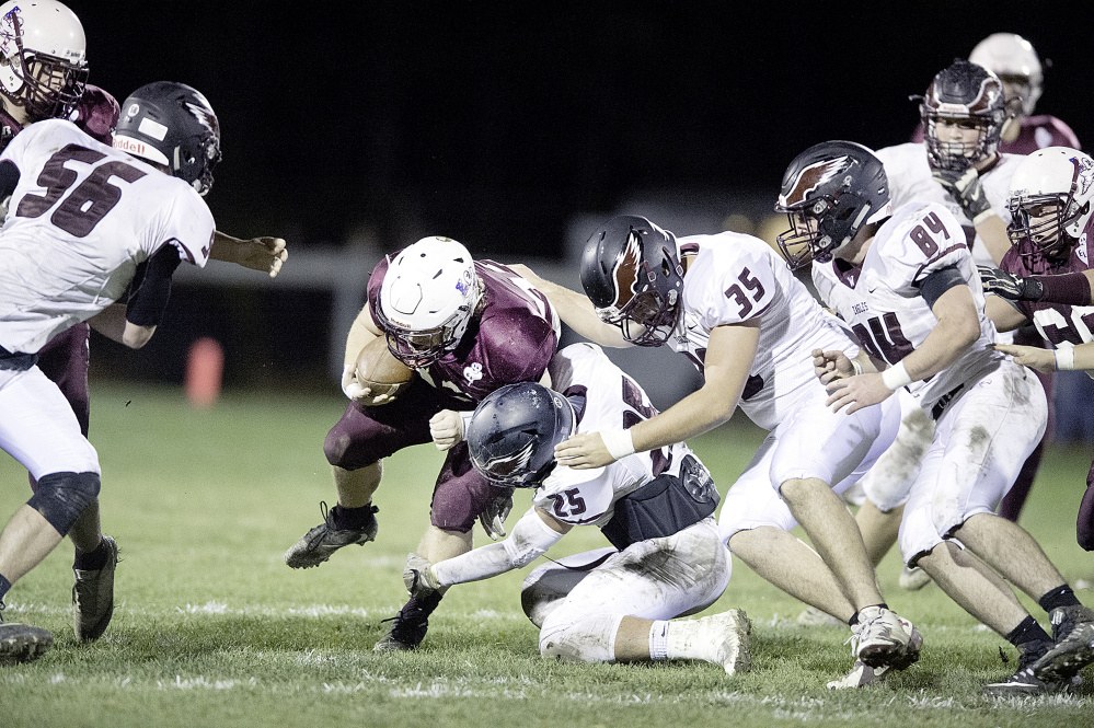 Windham defenders Nathan Watson (25), Logan Emerson (35) and Anthony Kilgallon try to tackle Edward Little's Caden Begos during their Class A North semifinal Friday night in Auburn. Windham beat the top-seeded Red Eddies, 21-12.