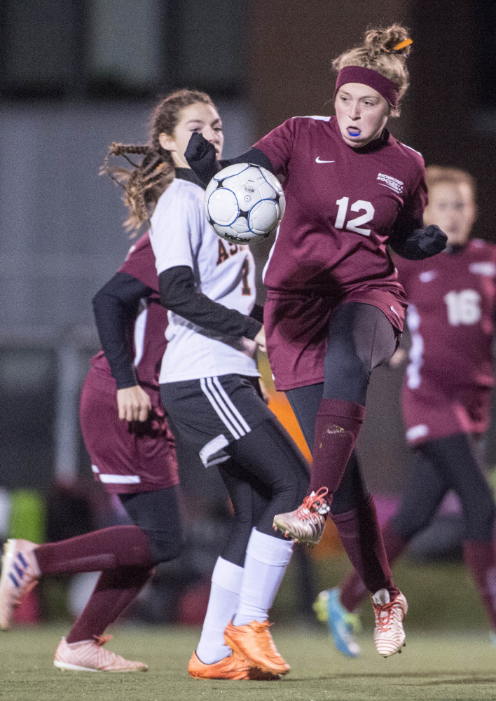Staff photo by Michael G. Seamans   Richmond's Ashley Brown (12) battles for the ball with Ashland's Danni Carter (1) in the Class D state championship game Saturday in Hampden.