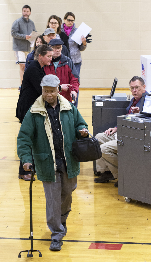 Joseph Kabalda finishes voting Tuesday at Reiche Elementary School in Portland. Residents faced questions on rent limits, zoning reform and school renovations.