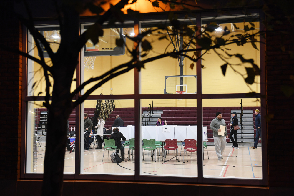 Seen through a window, people vote at Charles Houston Recreation Center in Alexandria. (Washington Post photo by Matt McClain)
