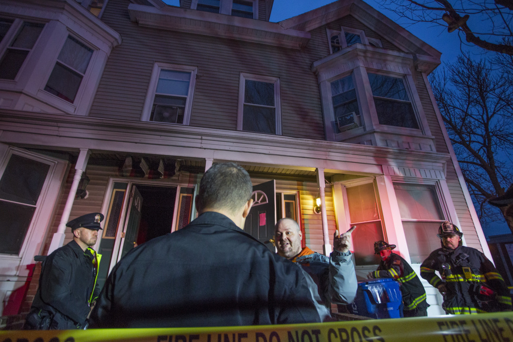 Peter Sullivan talks with investigators at the scene of a fire at 3 Sherman St. in Portland on Tuesday afternoon after a fire started in his apartment. Sullivan said he had to climb out his bedroom window to escape.