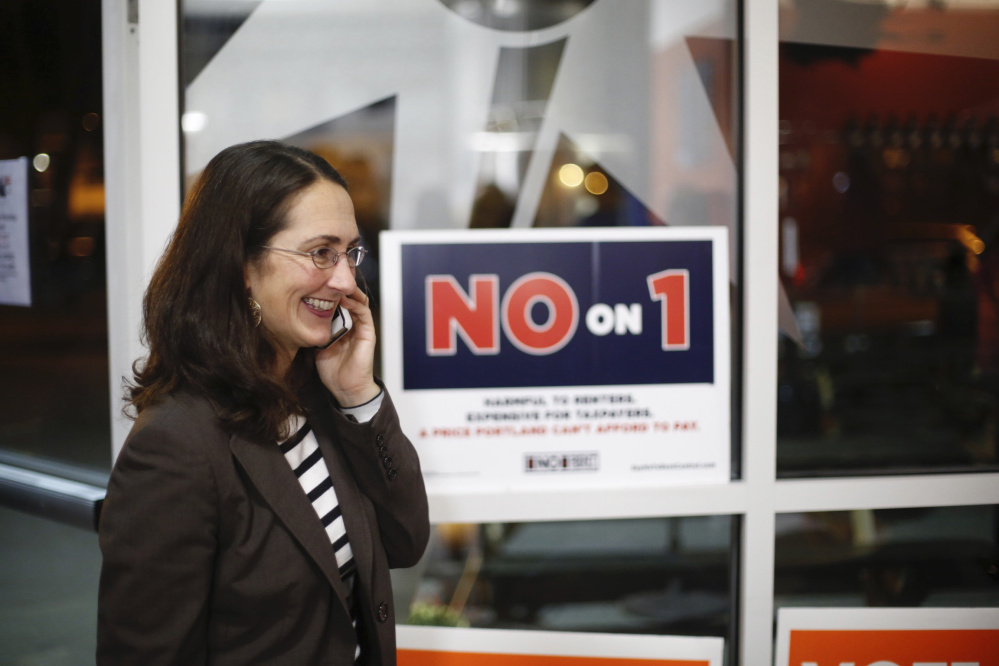 Yasmin Vitalius, the wife of the spokesman for Say No To Rent Control, talks on the phone at an election results gathering Tuesday.