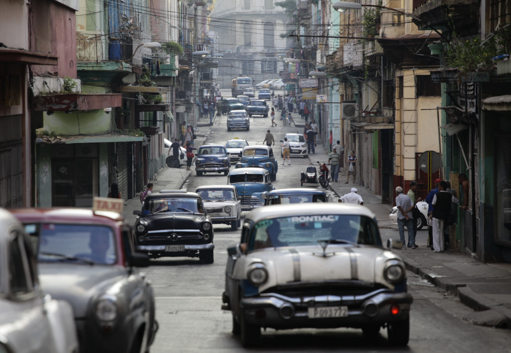 Old American cars used as collective taxis traverse a street in Havana. New restrictions on American travel to Cuba will hurt host families, guides and local farmers.