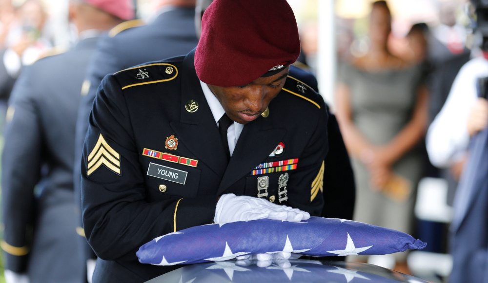 An honor guard member touches an American flag to the coffin of Sgt. La David Johnson, one of four soldiers killed in Niger, at a service on Oct. 21. The deaths should raise awareness that we're still engaged in the war on terrorism.