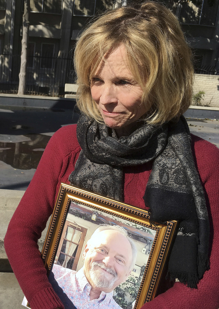 Teri McCall holds a photo of her late husband Jack McCall outside of a courtroom in Fresno, Calif., in January. California can require Monsanto to label its Roundup as a possible cancer threat, a judge tentatively ruled Friday.